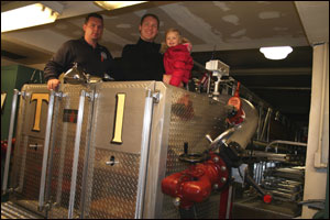 Eric, Pat, and Greta on a fire truck